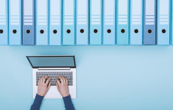Person typing on a laptop below binder folders
