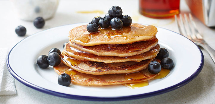 A stack of banana pancakes topped with blackberries, served on a circular plate.