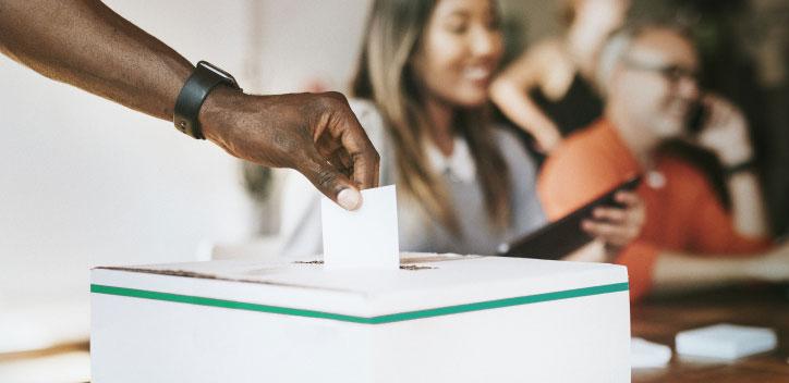 Person dropping vote into a ballot box