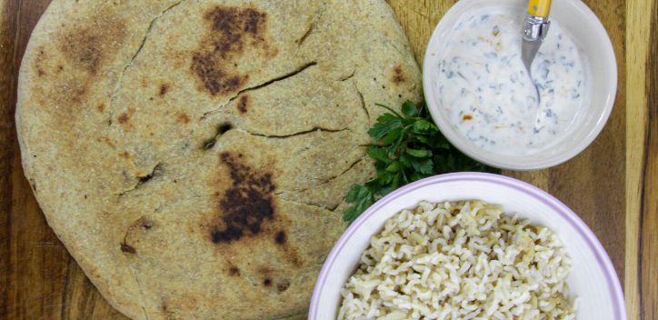 A filled flatbread served on a wooden board, with a small bowl of soya yoghurt dressing, and a bowl of rice served on the right hand side.