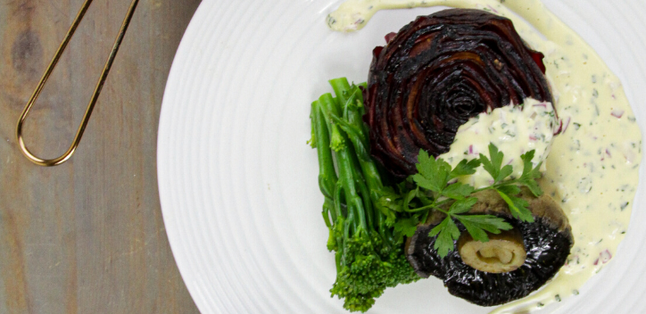 A beetroot stake served with stem broccoli, flat mushrooms and a soya cream sauce on a round plate.