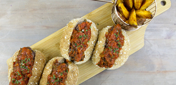 A selection of bread rolls filled with black bean marina sauce next to a side of potato wedges, served on a wooden platter.
