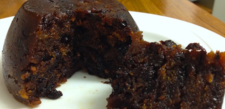 Vegan Christmas pudding served on a round plate.