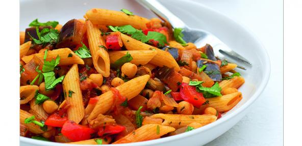 A shallow bowl of penne paste with aubergine and chickpeas.