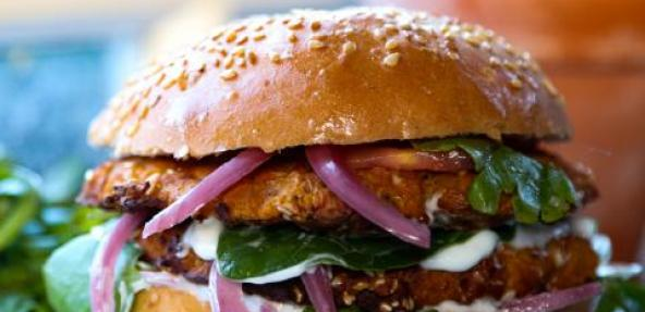 Chickpea & pumpkin burger served with red onions, green leaf and vegan mayonnaise in a bun