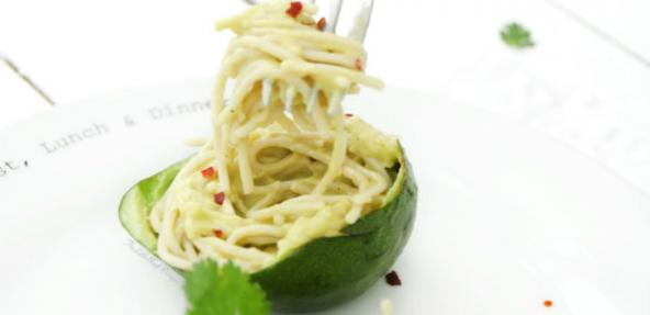 Half an avocado on a plate filled with creamy spaghetti, partly raised and twisted around a fork.