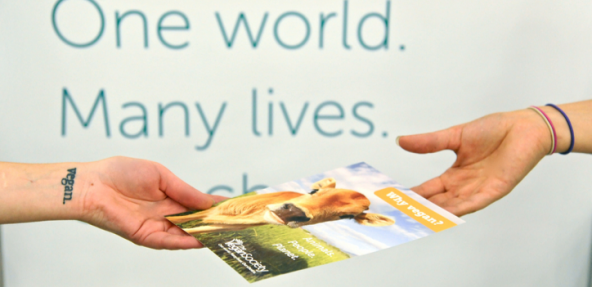 Hands exchanging a Vegan Society leaflet