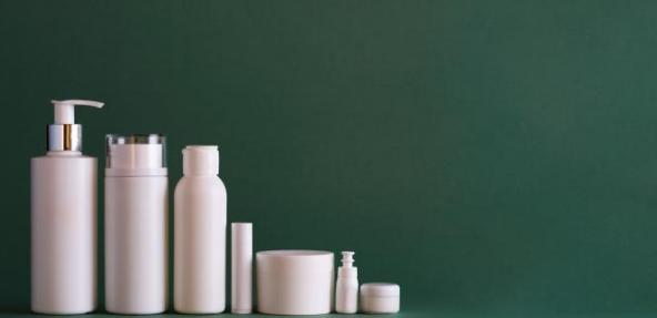 Cosmetic and beauty bottles in white with green background