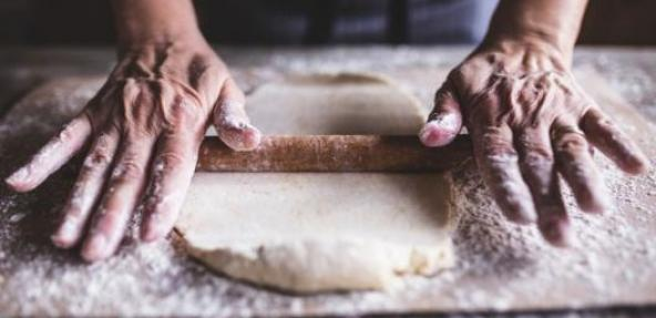 Hands rolling dough with rolling pin