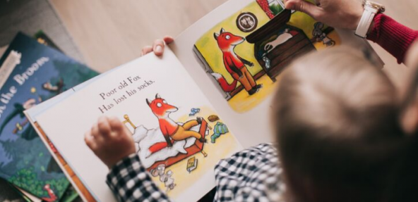 child reading a story book about a fox