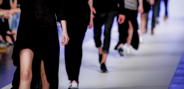 Model on catwalk photographed from the neck down with other models walking behind