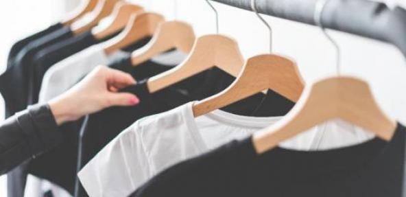 Black and white t shirts hanging on a clothes rail