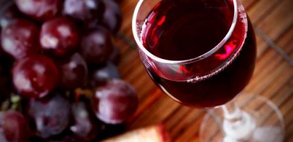 Glass of red wine next to red grapes
