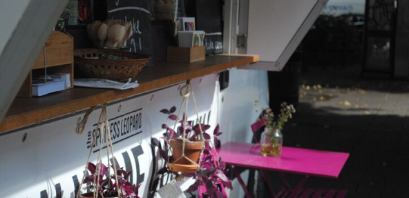 Close up of pink metal table and chairs outside of food van with hanging plant pots