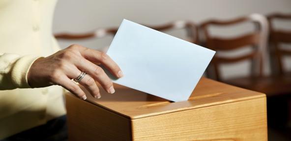 person voting in a ballot box
