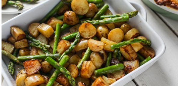A square dish filled with roasted new potatoes and asparagus.