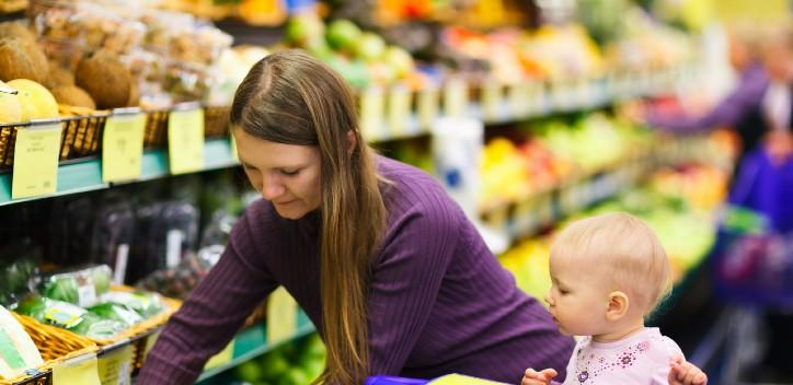 Lady with a baby shopping for fruit and veg in a supermarket