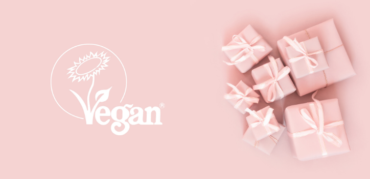 Pink gift boxes against a pink background with the Vegan Trademark sunflower logo on white