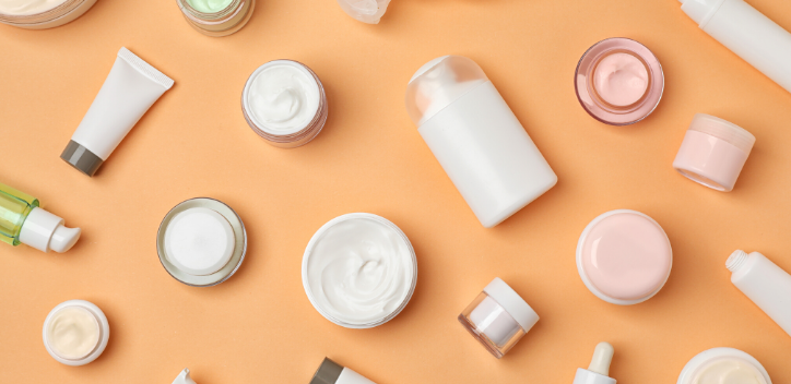 Plain cosmetics pots containing product, scattered across a peach coloured background.