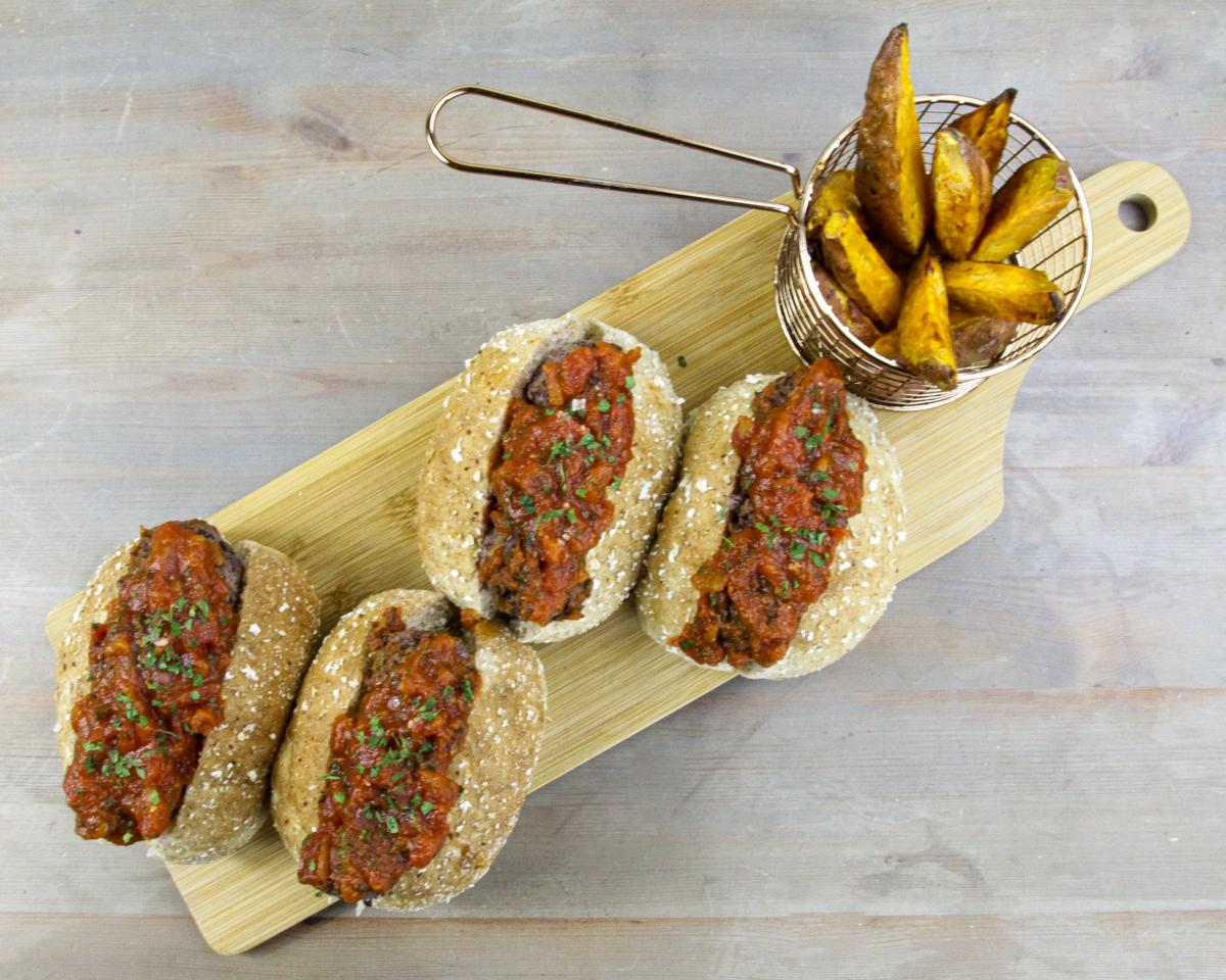 four vegan black beanball marinara subs and a small metal basket of wedges on a wooden board against a grey background