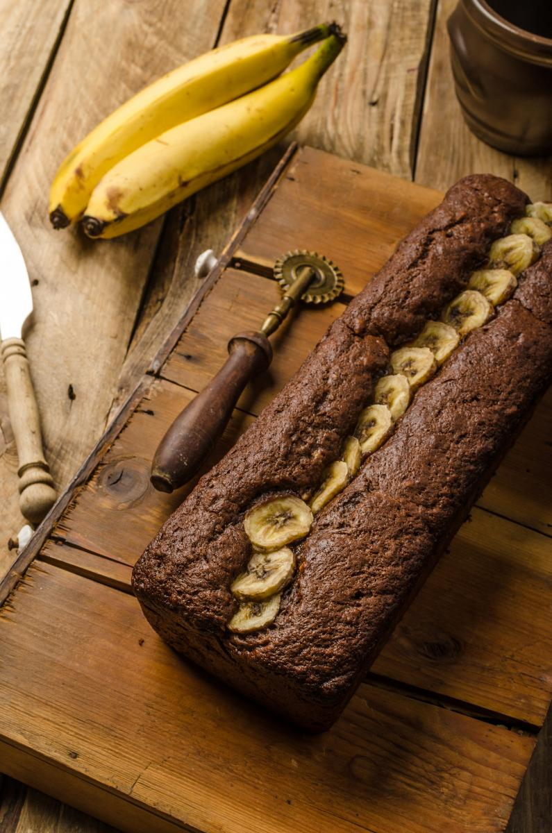 A loaf of banana bread topped with banana slices served on a wooden board.