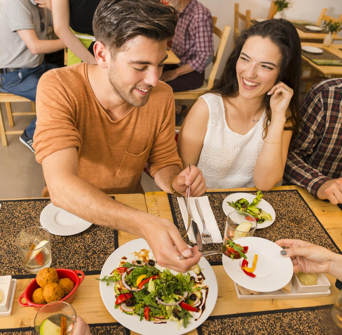 Laughing people sharing salad at a table