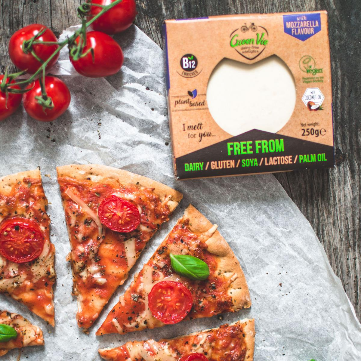 Cheese and tomato pizza cut up next to Green Vie cheese in packaging