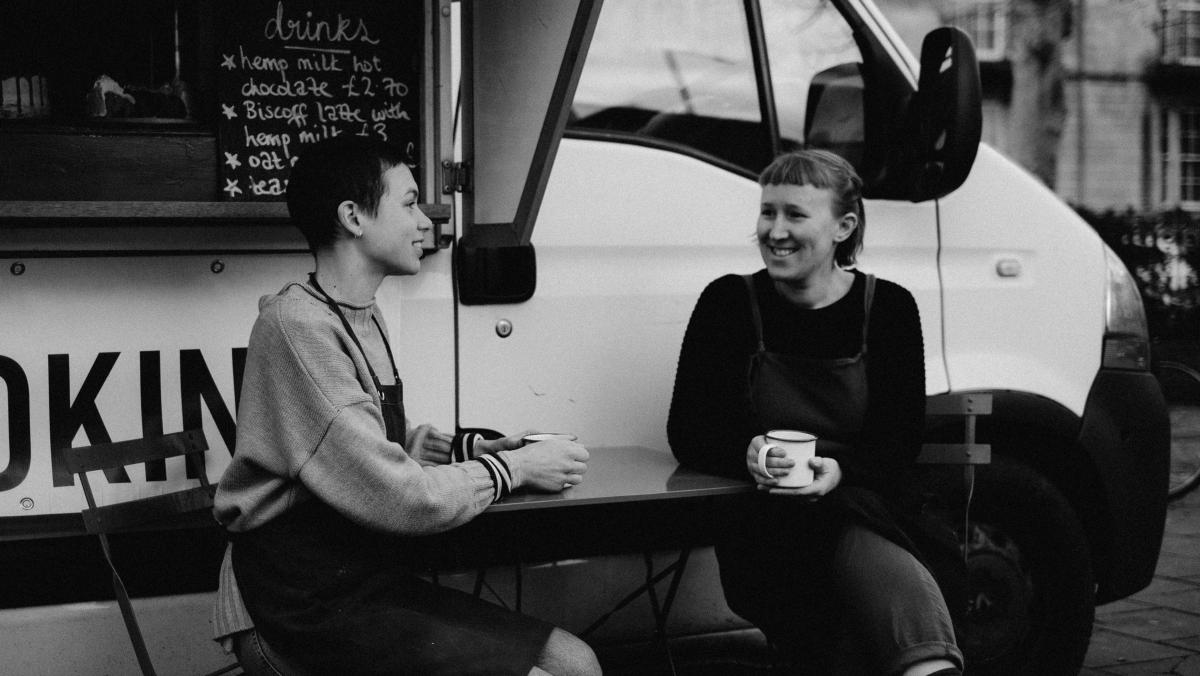 Black and white image of two women sat outside of a vegan food van image talking and smiling