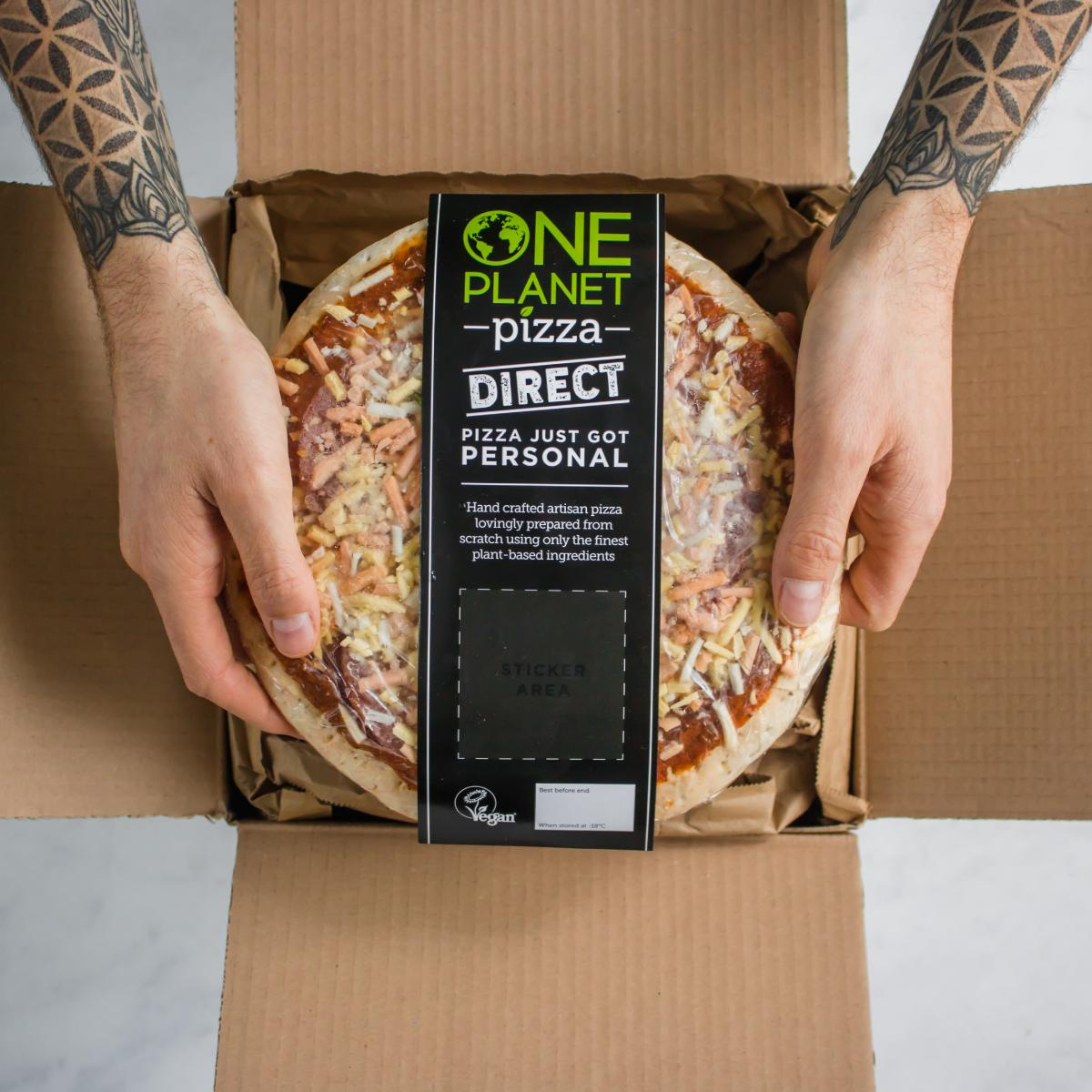 Tattoo'd persons hands holding a pizza in a cardboard box