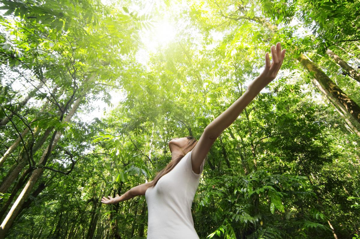 young woman standing in forest with arms raised