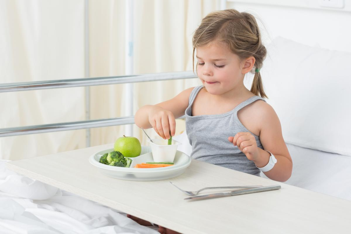 Child in hospital bed eating veggies