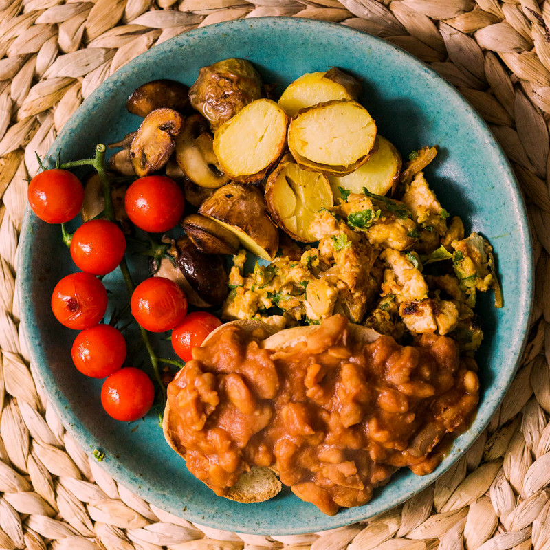 Day Radley's scrambled tofu recipe plate up with potatoes, tomatoes and beans.